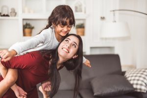 Mother giving piggyback ride to daughter